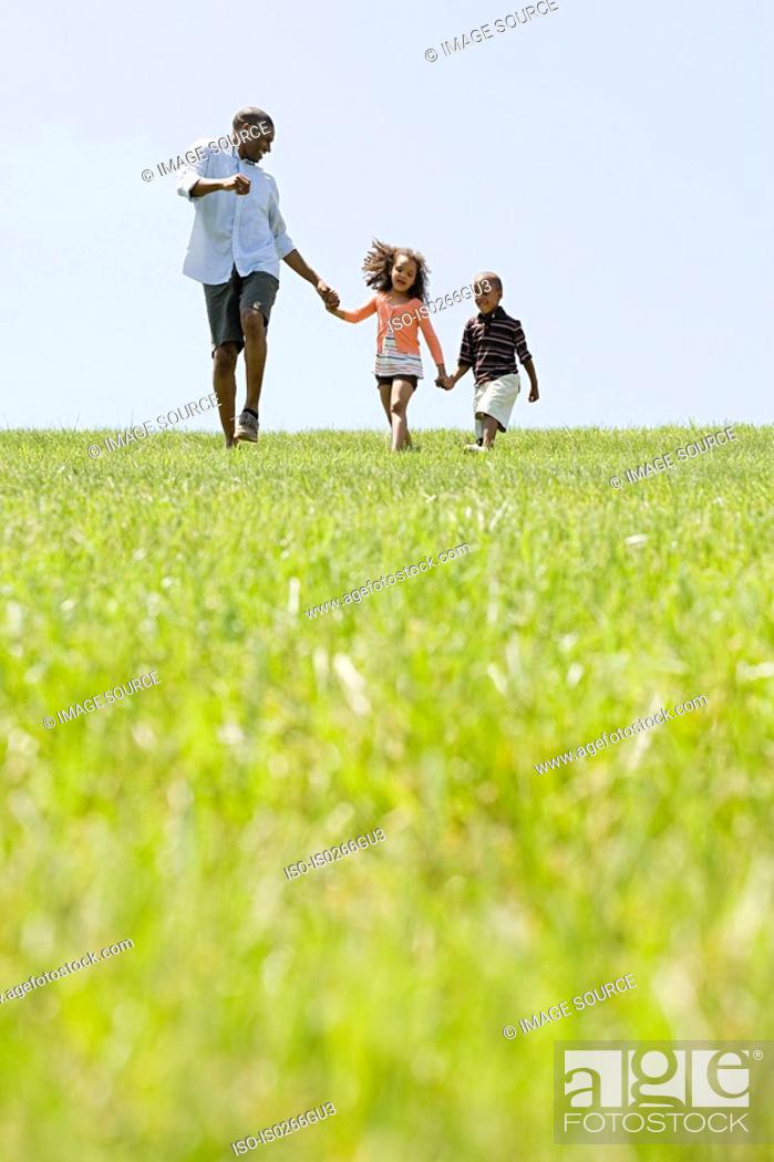 Stock Photo: Father and children in field.