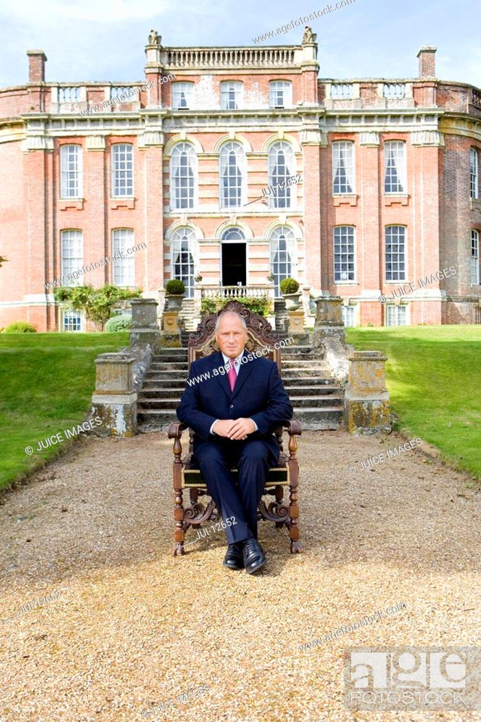Stock Photo: Mature man on chair in grounds of manor house, portrait.