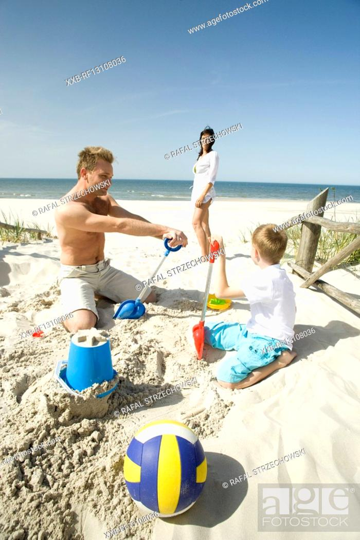 Stock Photo: family building sand castle.