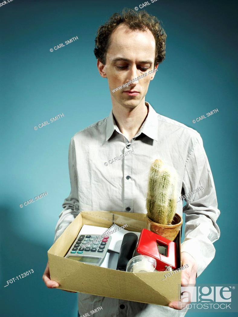 Stock Photo: A man carrying a box of possessions after being fired.