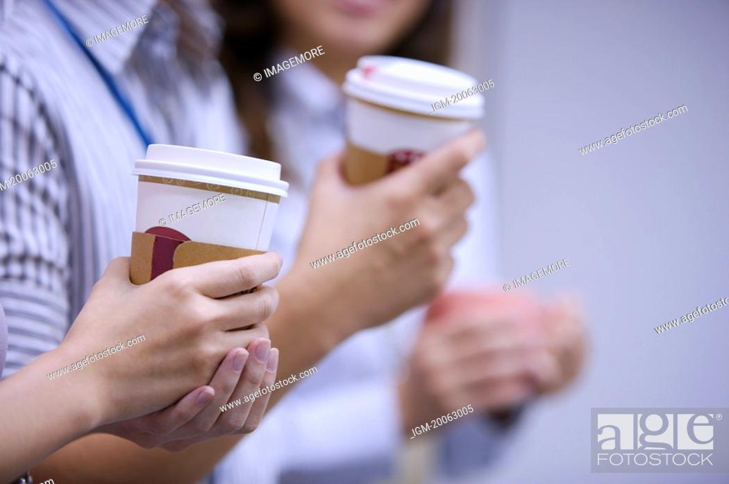 Stock Photo: Colleagues holding drink for coffee break.