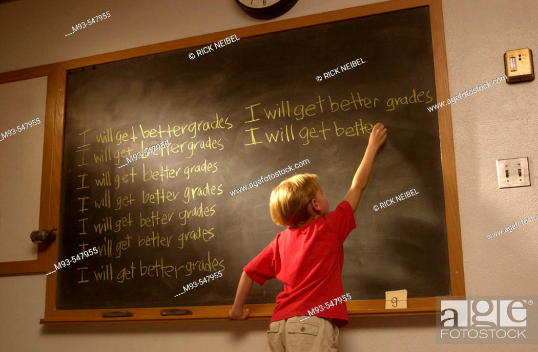 Stock Photo: Young blond boy; red t-shirt; at wood-framed classroom blackboard writing 'I will get better grades'multiple times. Light highlighting blackboard and boy's.