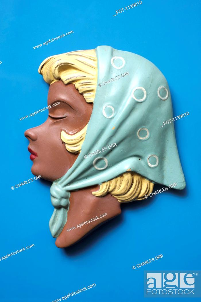 Stock Photo: A retro wall hanging of a woman with blond hair and a headscarf.
