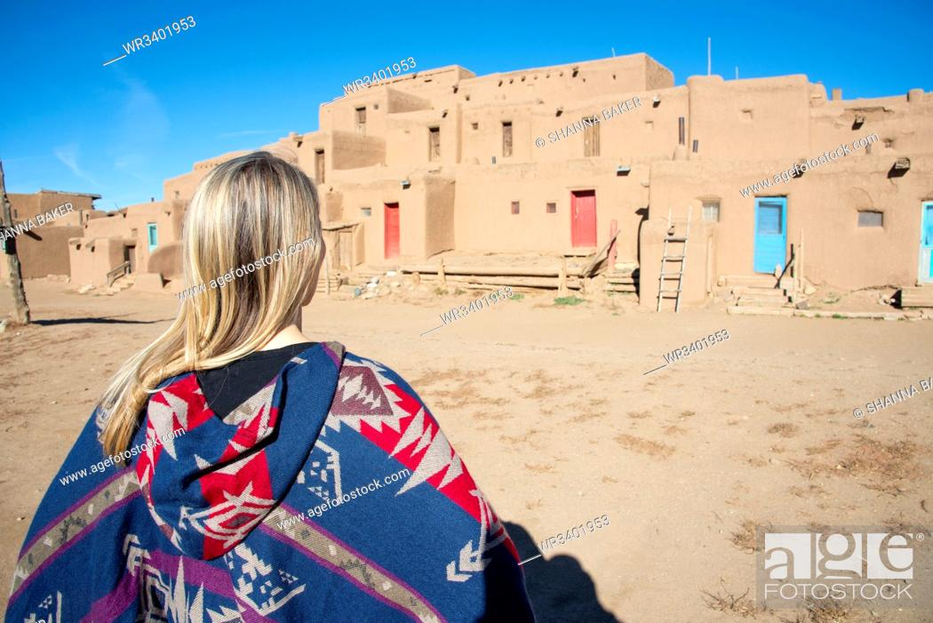 Stock Photo: Woman standing in front of Taos Pueblo, UNESCO World Heritage Site, Taos, New Mexico, United States of America, North America.
