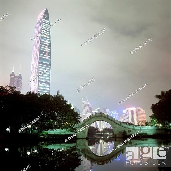 Stock Photo: View of illuminated city buildings across water at night, Shenzhen, China.