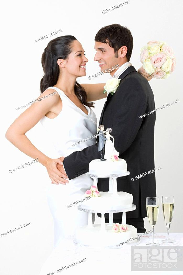 Stock Photo: Newlyweds standing near wedding cake.