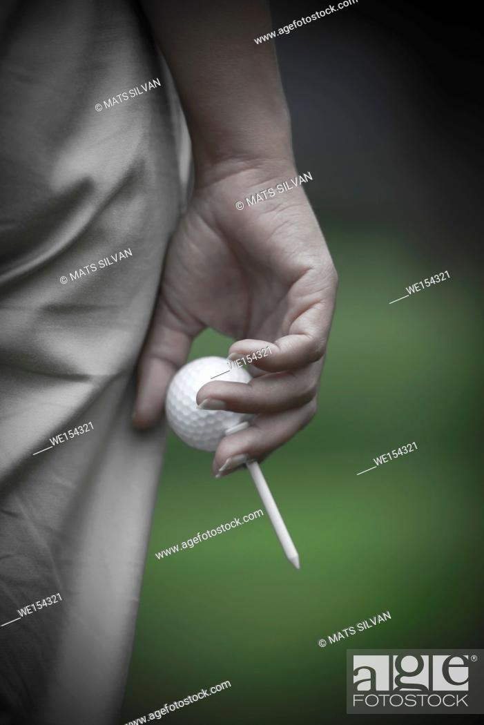 Stock Photo: Golfer Holding a Golf Ball and a Tee in Switzerland.