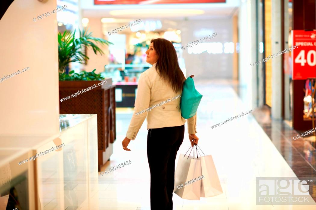 Stock Photo: Mature woman with shopping bags in shopping mall, Dubai, United Arab Emirates.