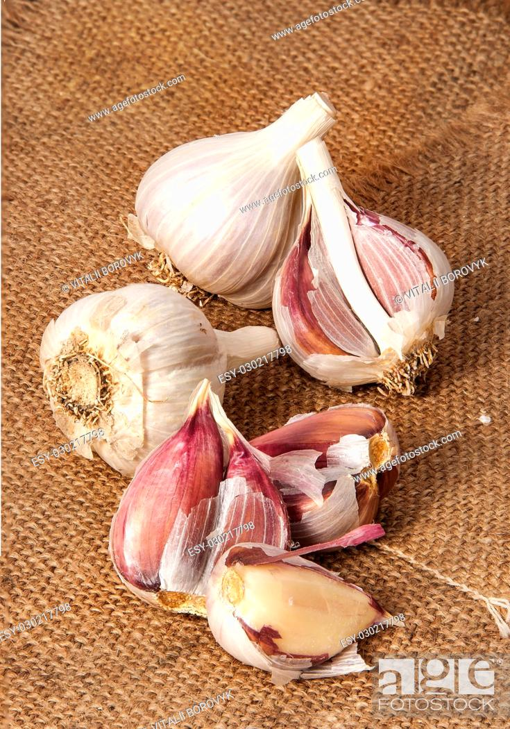 Stock Photo: Garlic wholly and cloves scattered on sackcloth.
