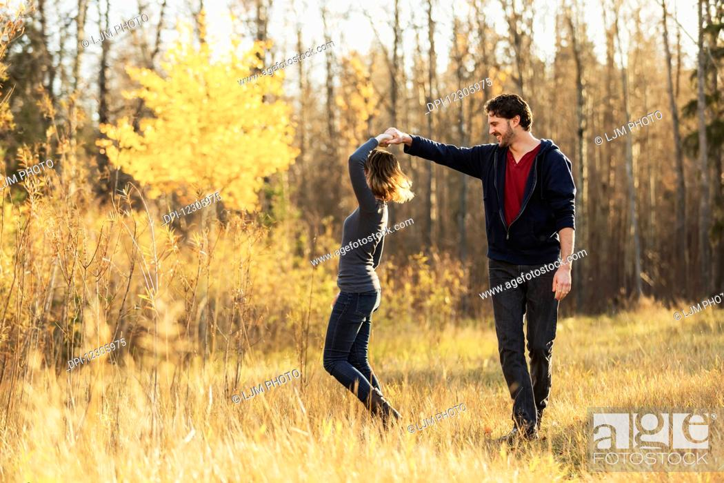 Stock Photo: A young couple walking and pretending to dance in a city park in autumn; Edmonton, Alberta, Canada.