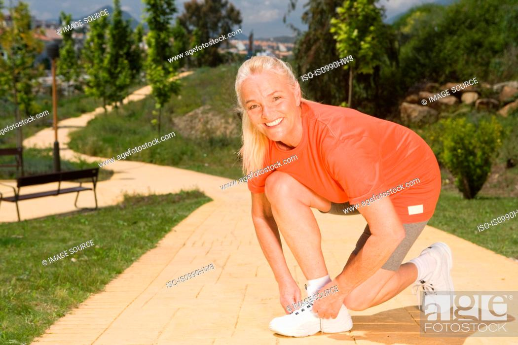 Stock Photo: Mature woman runner tying shoelaces.