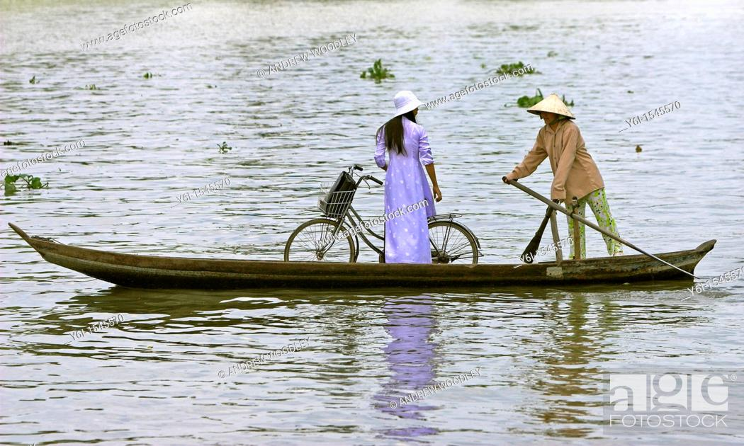 Stock Photo: Woman in conical hat paddlling woman in ao dai with bicycle in ferry boat across Mekong Delta river Vietnam.