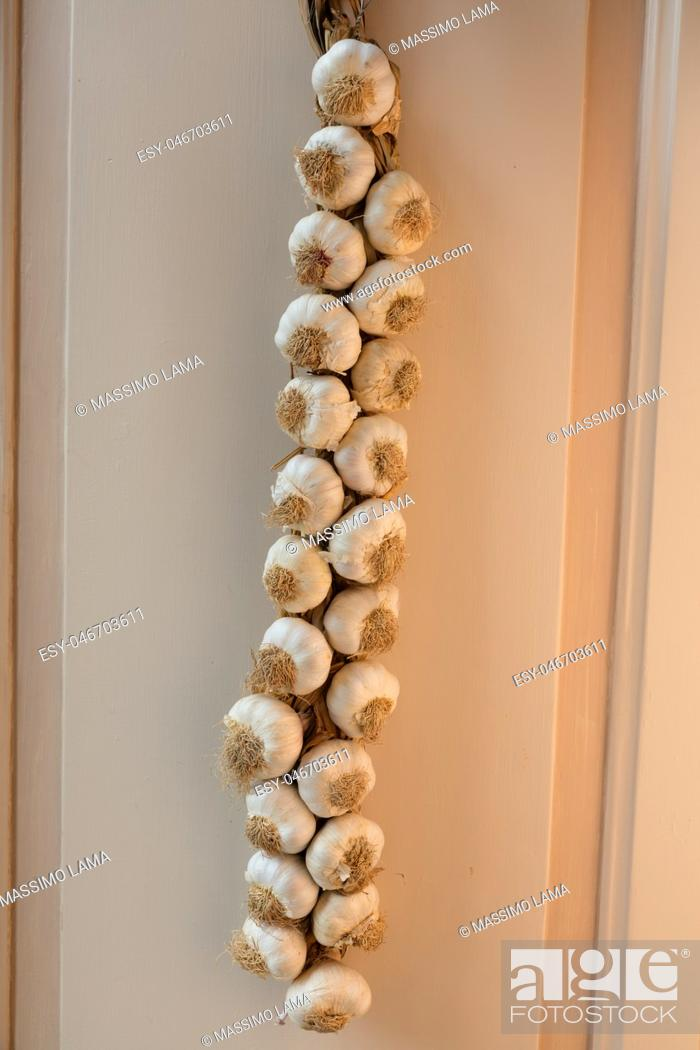 Stock Photo: Neapolitan garlic braid leaning against the wall.