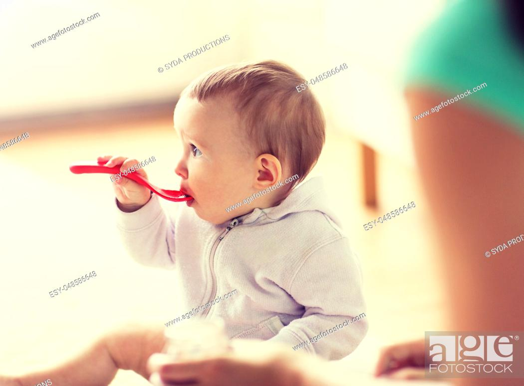 Stock Photo: mother and baby with spoon eating at home.