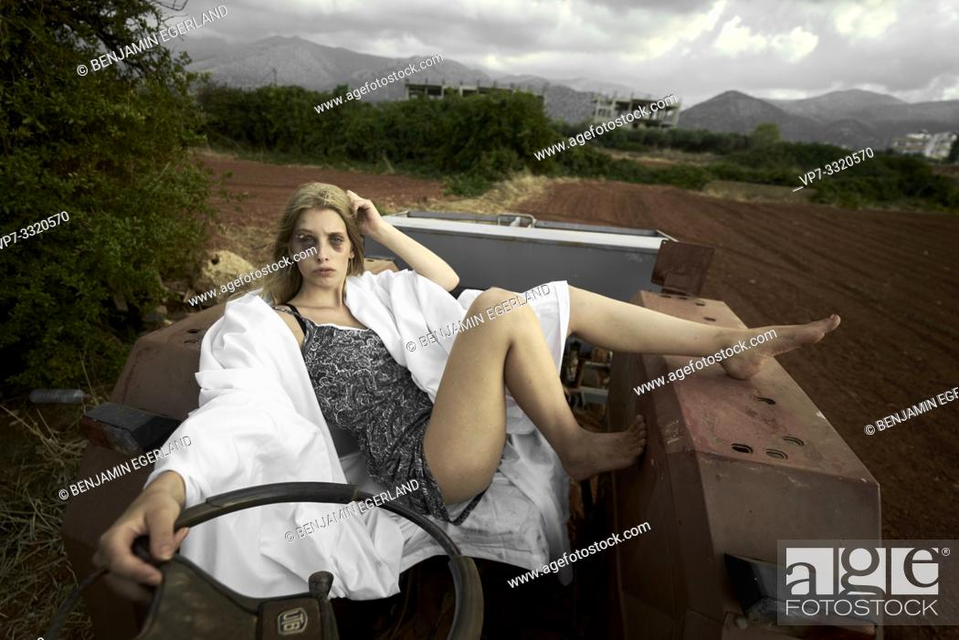 Stock Photo: young defaced teenage woman with black eye and voluptuous body sitting on tractor at rural farm, scars.