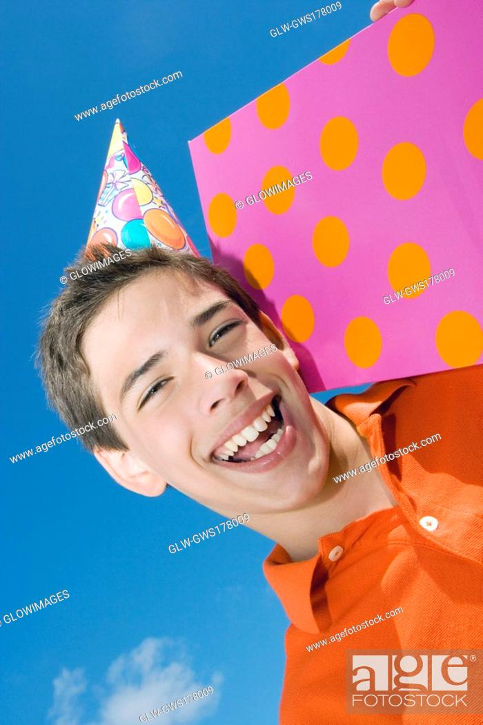 Stock Photo: Portrait of a boy holding a birthday present and laughing.