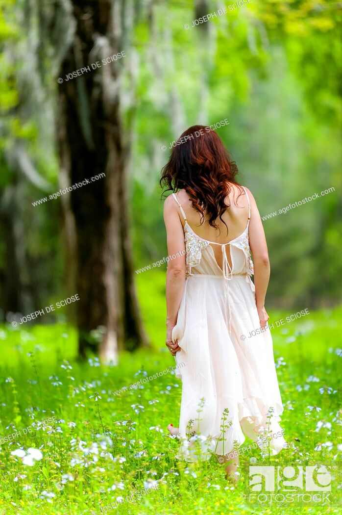 Stock Photo: Back view of brunette woman wearing a white dress walking in a field of flowers.