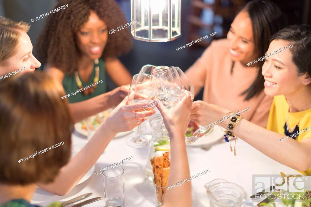 Stock Photo: Smiling women friends toasting white wine glasses dining at restaurant table.