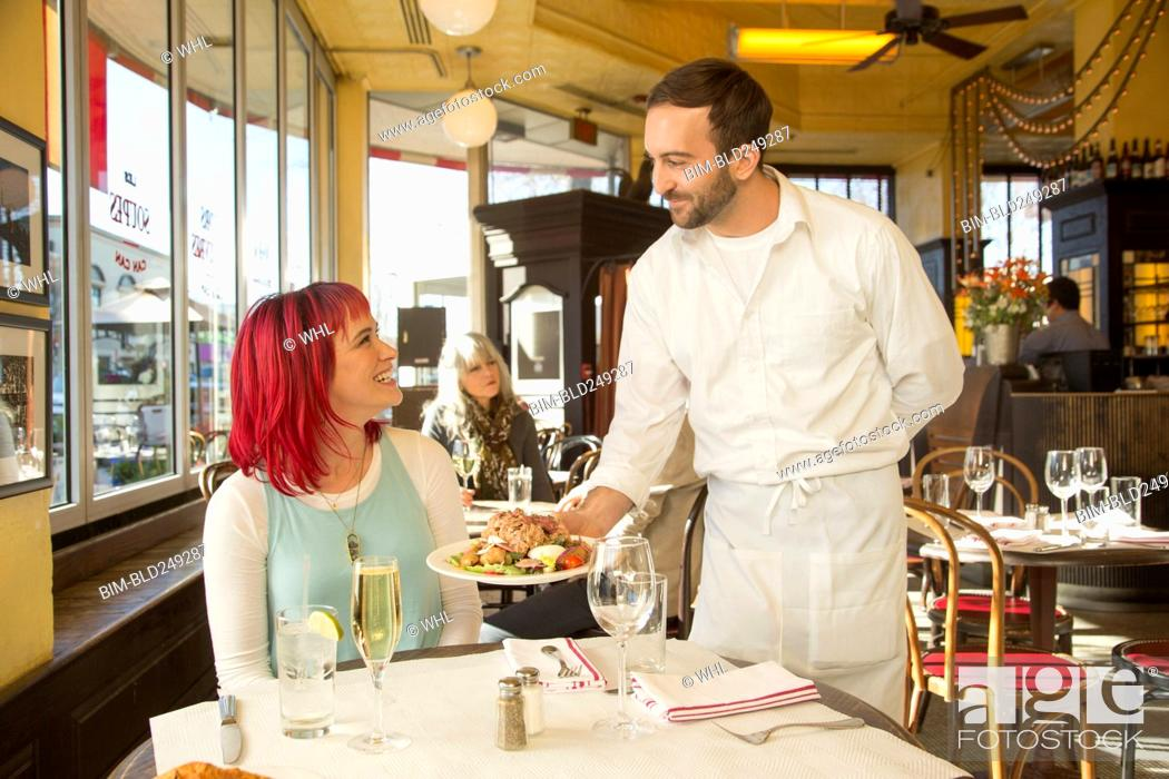 Stock Photo: Caucasian waiter serving plate to customer.