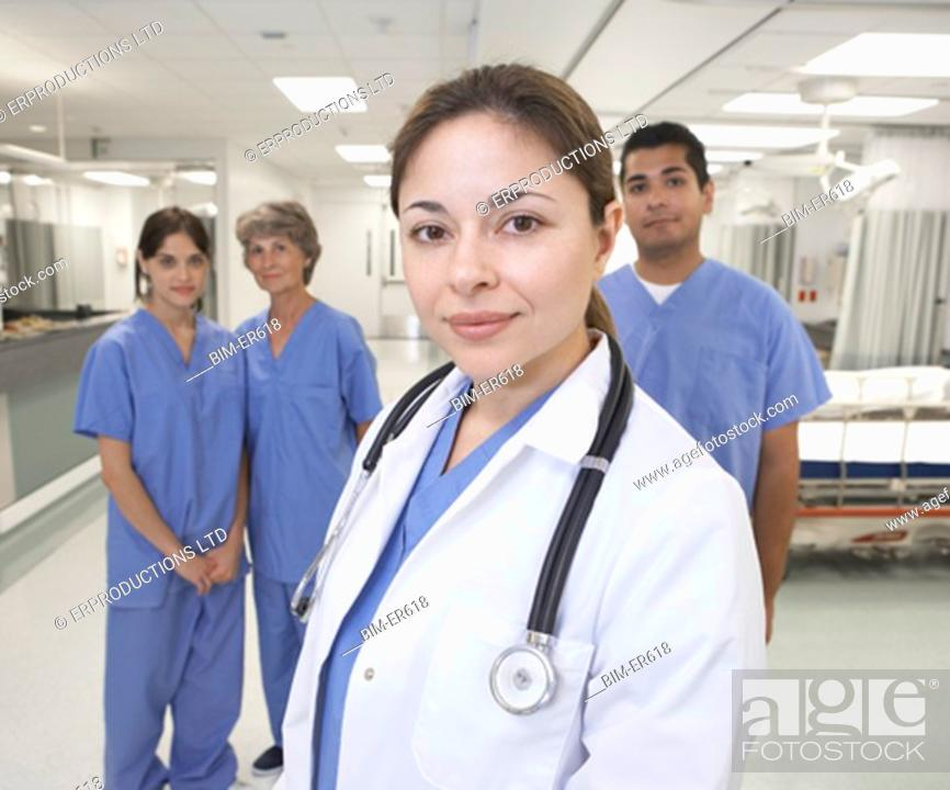 Stock Photo: Hispanic female doctor with nurses in background.