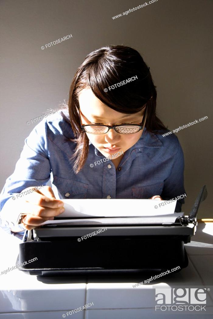 Stock Photo: Woman sitting in chair typing on typewriter in kitchen.