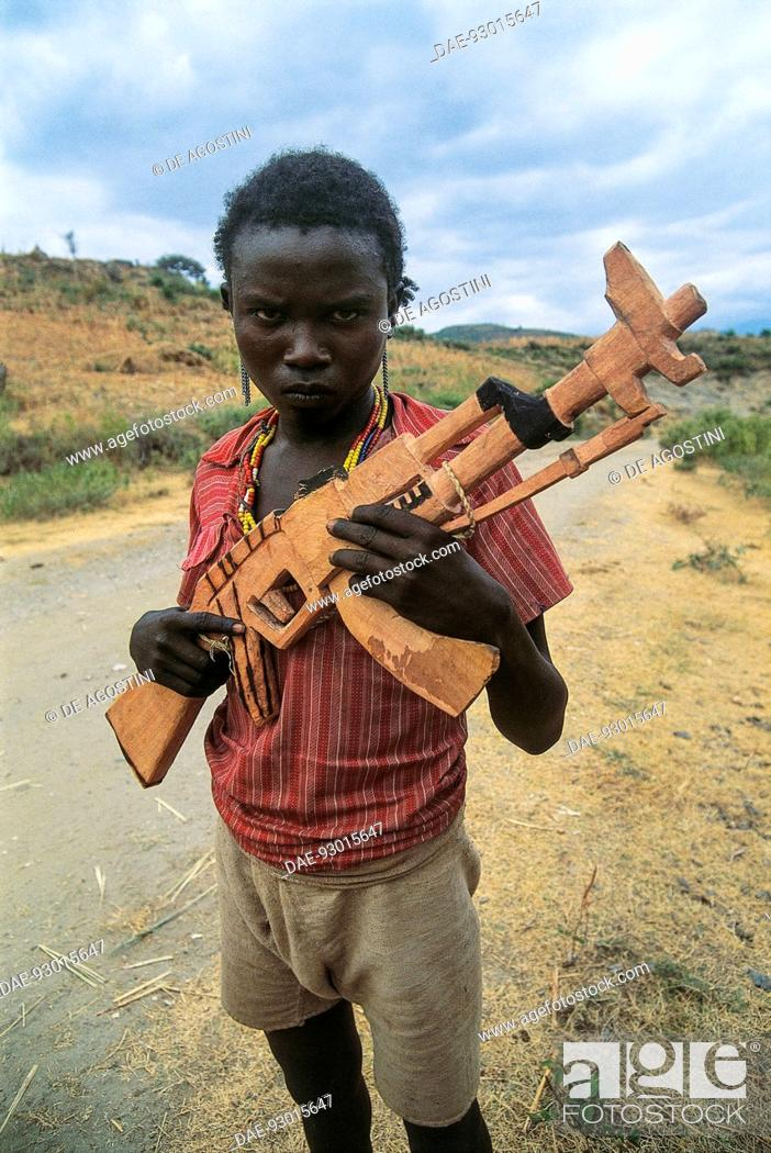 Child with wooden toy weapon, copied from a Kalashnikov