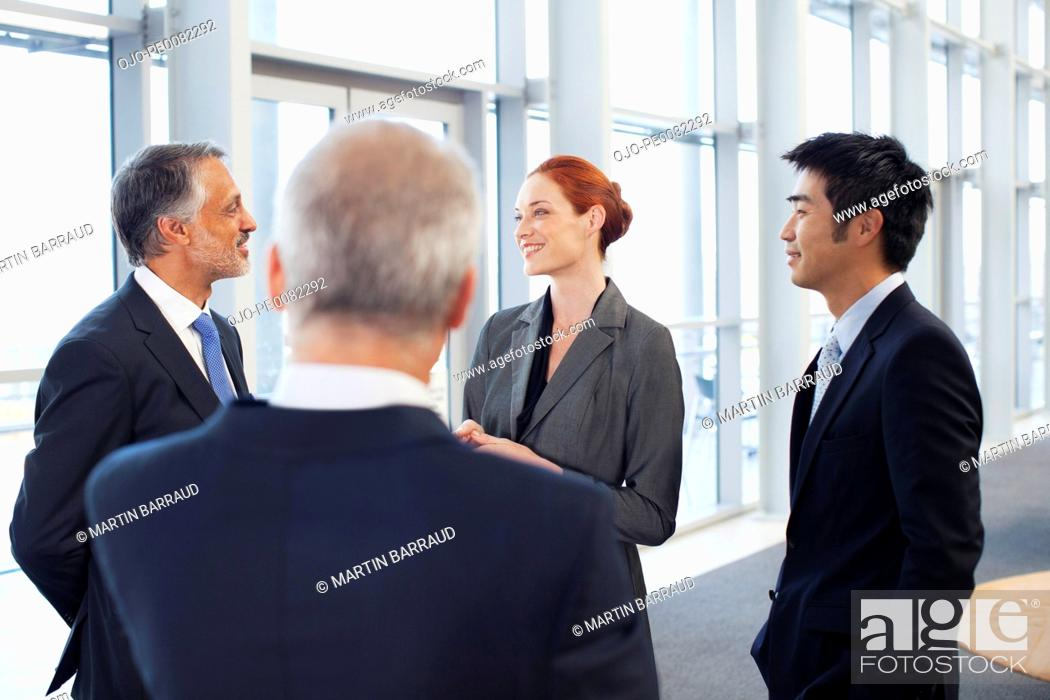 Stock Photo: Business people talking in office lobby.