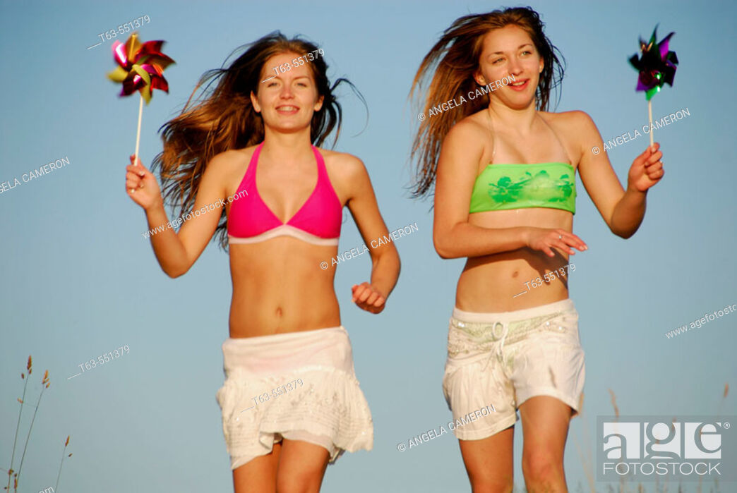 Stock Photo: girl 13, girl 18 yrs running with pinwheels at the beach.