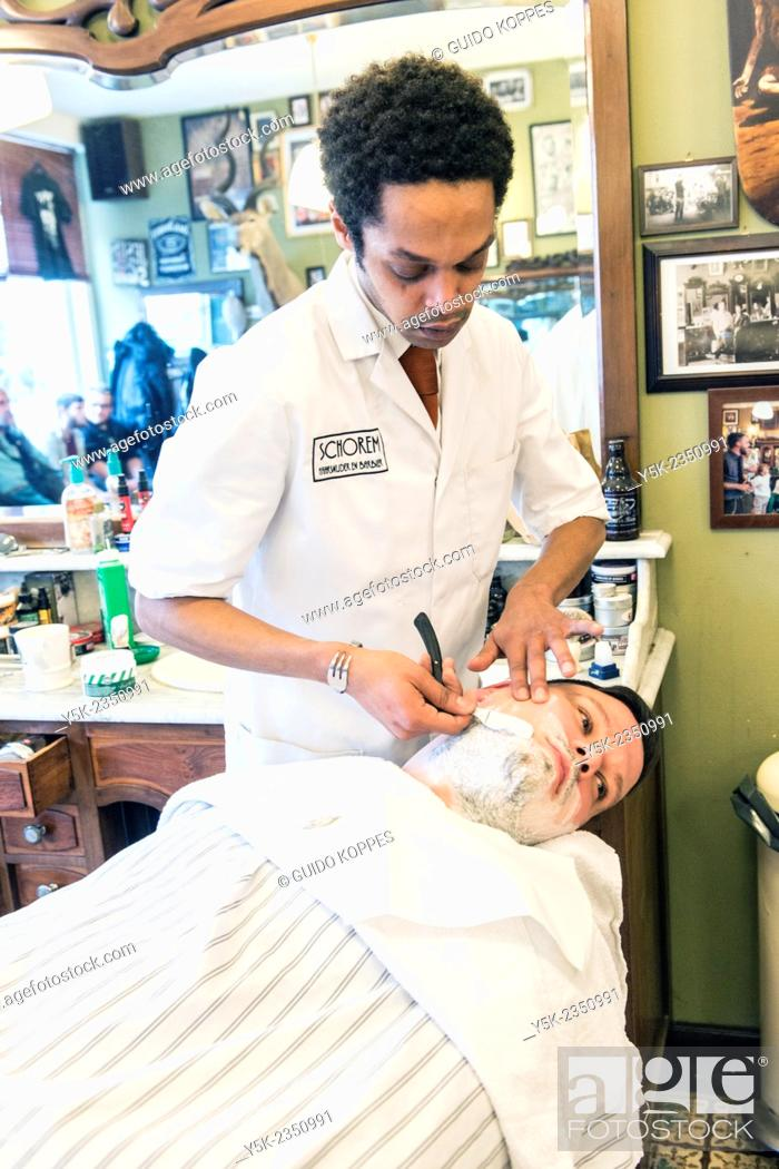 Stock Photo: Rotterdam, Netherlands. Barber store Schorem. Male customer lying back in his barber chair while receiving a wet shave.