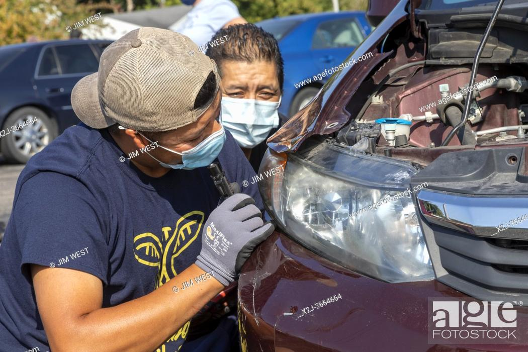 Stock Photo: Ypsilanti, Michigan - Professional and amateur auto mechanics made free car repairs at a Pull Over Prevention Clinic. The event aimed to help community members.