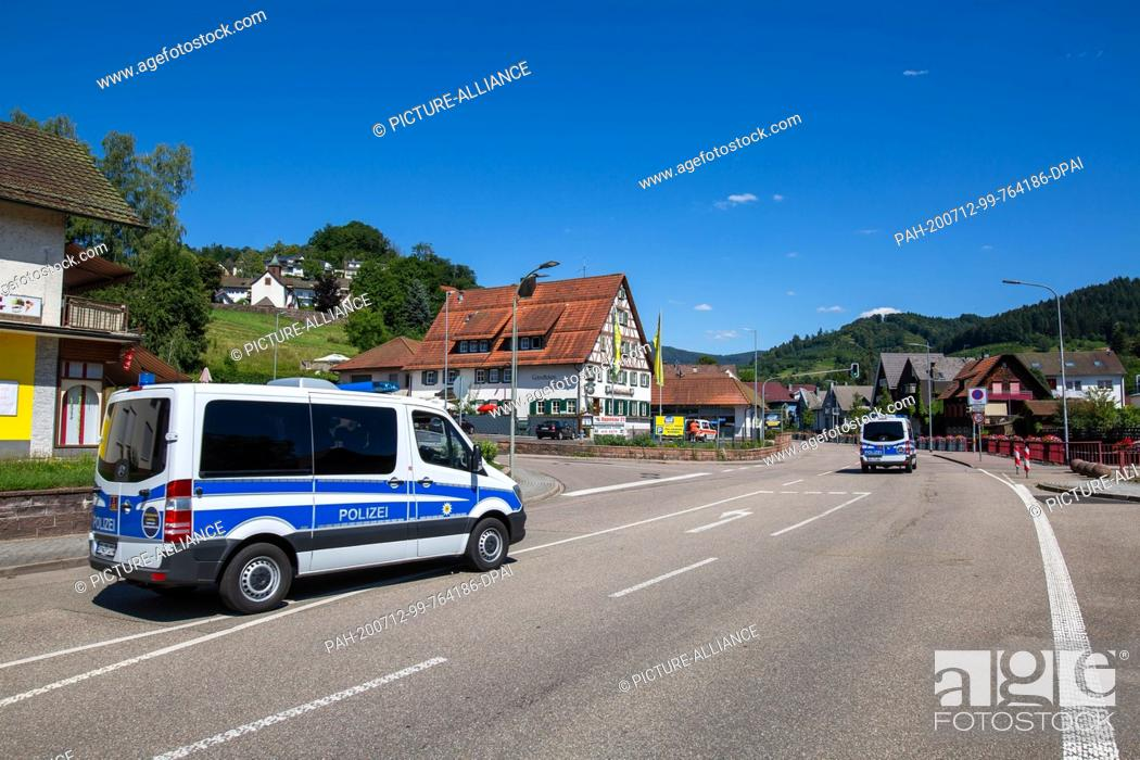 Stock Photo: 12 July 2020, Baden-Wuerttemberg, Oppenau: Two police vehicles drive through the community. A large police force has been searching for an armed man since this.