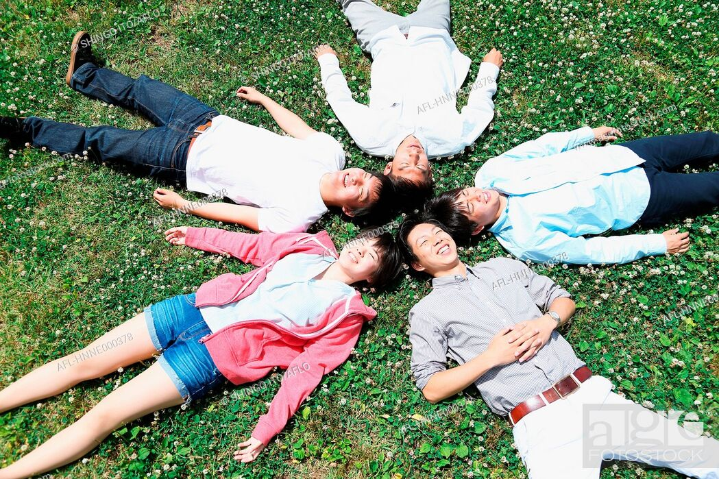 Stock Photo: Group of young Japanese friends laying on grass.