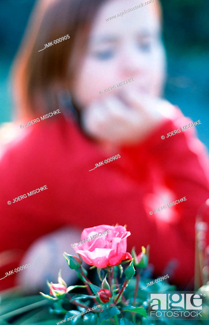 Stock Photo: Little girl in the garden, looking at a rose.