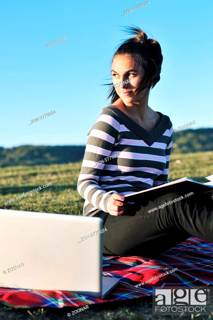 Stock Photo: young teen girl read book and study homework outdoor in nature with blue sky in background.