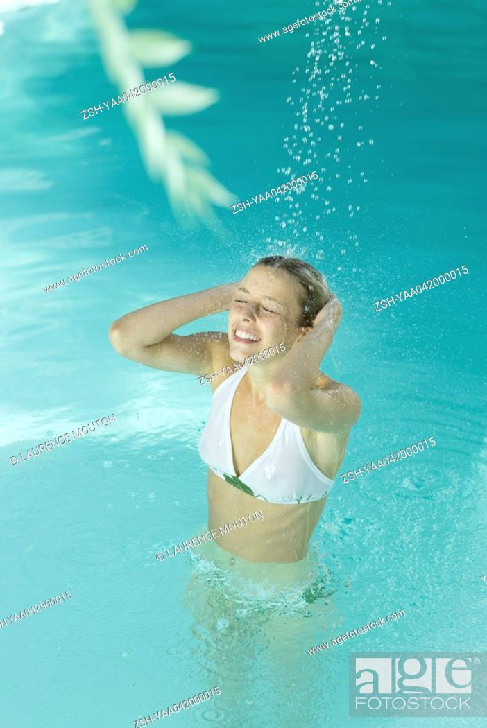 Stock Photo: Young woman standing in pool under spray of water.
