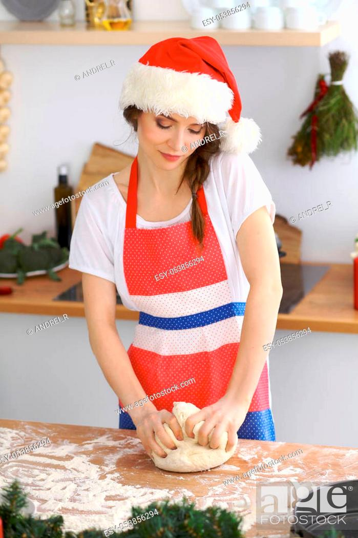 Stock Photo: Young brunette woman cooking pizza or handmade pasta while wearing Santa Claus cap in the kitchen. Housewife preparing dough on wooden table.