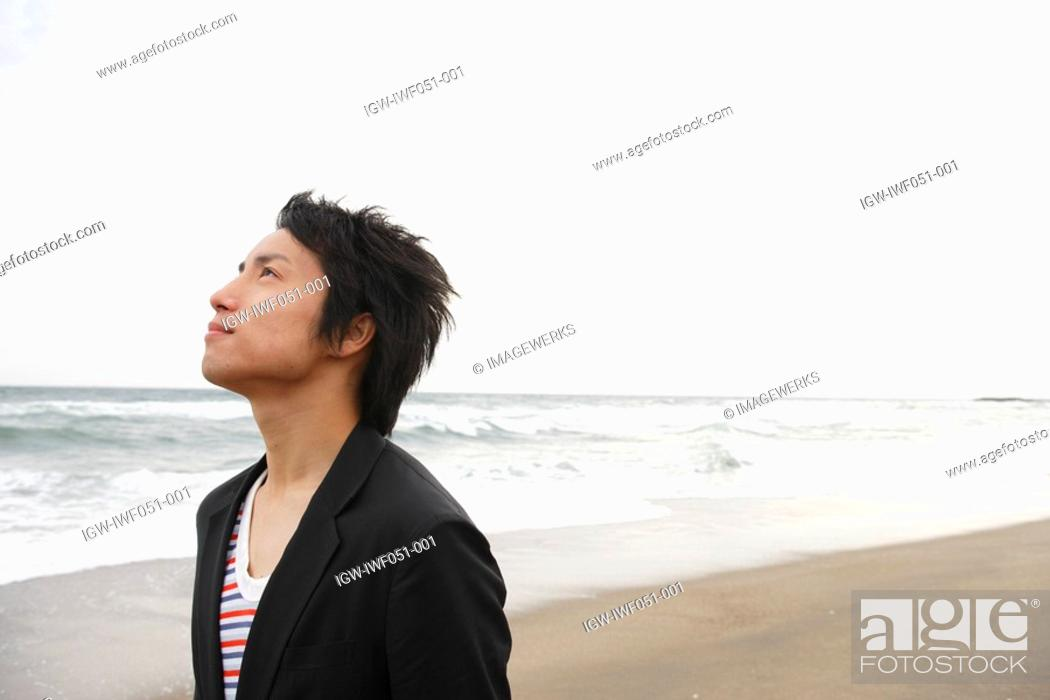 Stock Photo: Young man at beach, looking up.