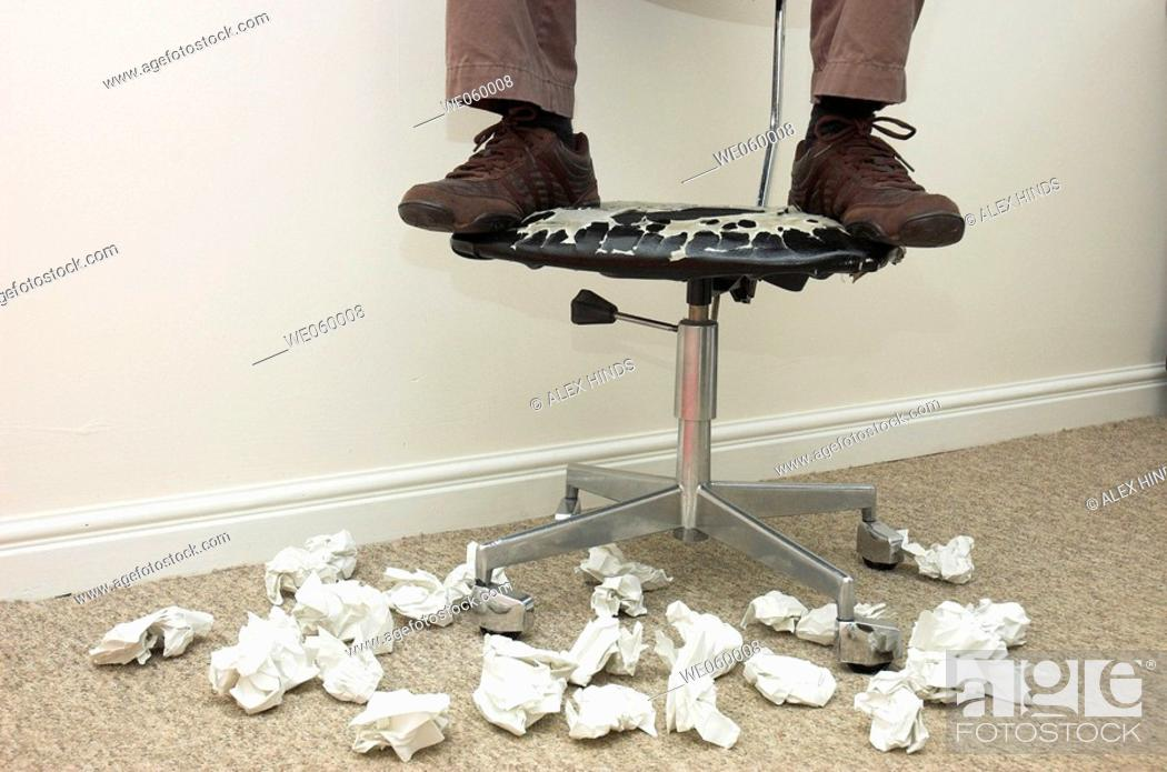 Stock Photo: Man's feet on battered office chair surrounded by crumpled paper.