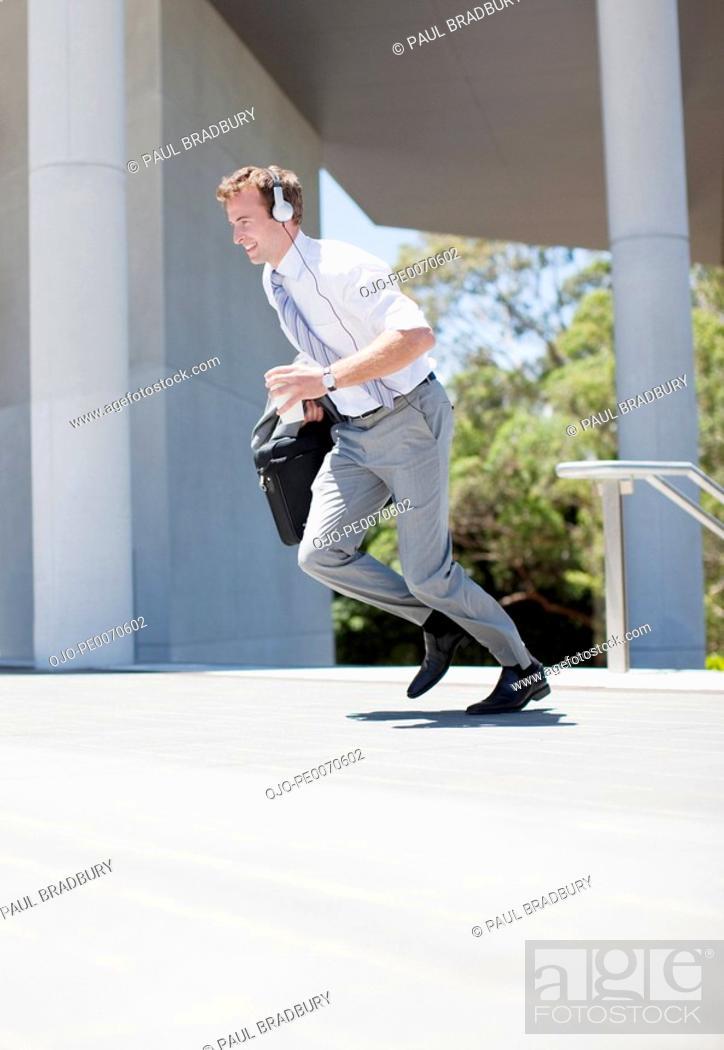 Stock Photo: Businessman in headphones running outdoors.