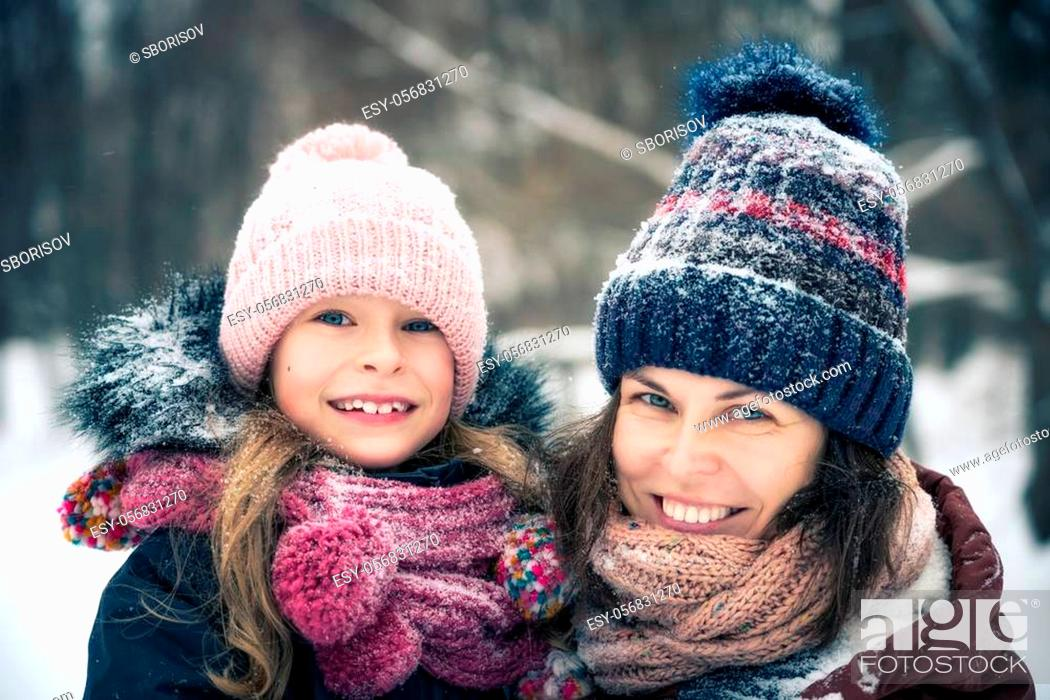Imagen: Little girl and her mother playing outdoors at winter day. Active winter holydays concept.