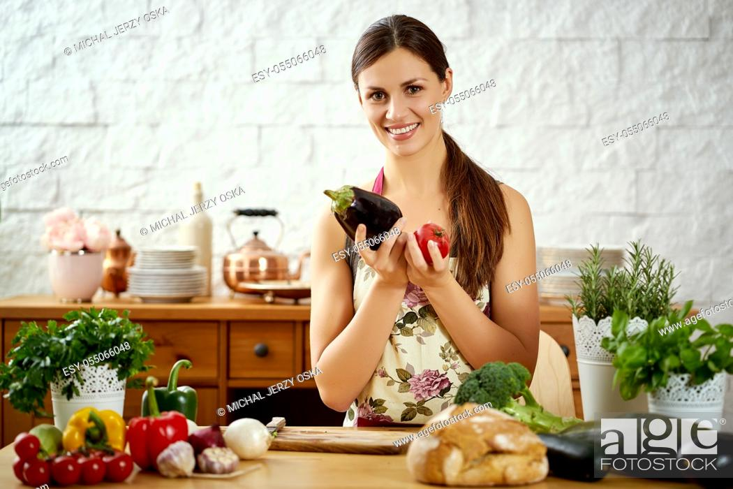 Stock Photo: beautiful young woman, brunette holds aubergine and tomato in the kitchen at a table full of organic vegetables.