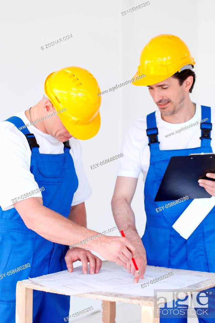 Stock Photo: Building, construction, development, teamwork and people concept - close up of builders in hardhats working with blueprint.