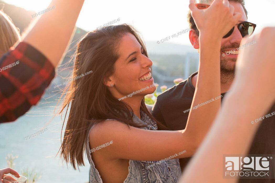 Stock Photo: Adult friends dancing at roof terrace party on waterfront, Budapest, Hungary.