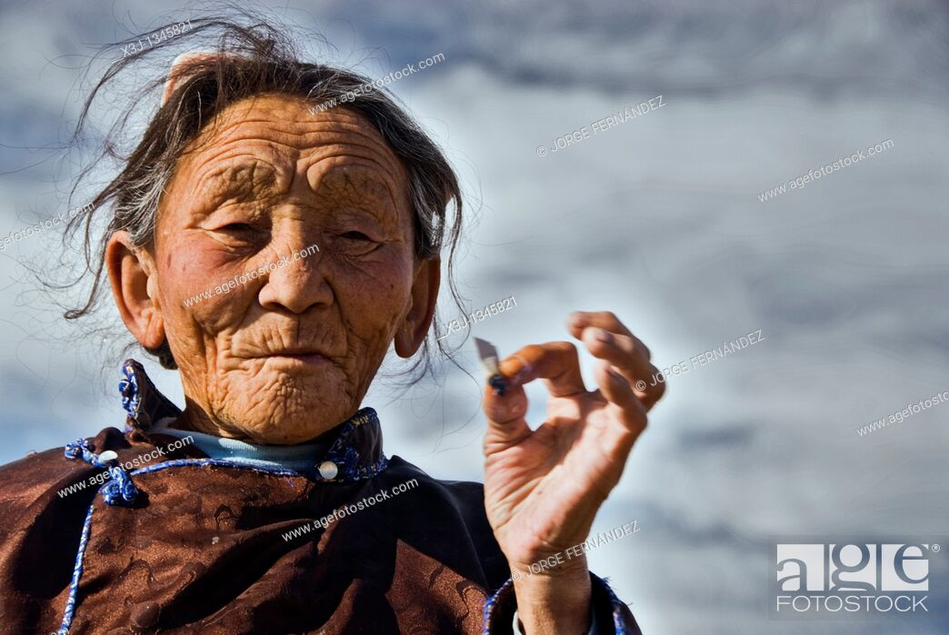 Stock Photo: Old Mongolian woman smoking a cigarette, Mongolian steppe.