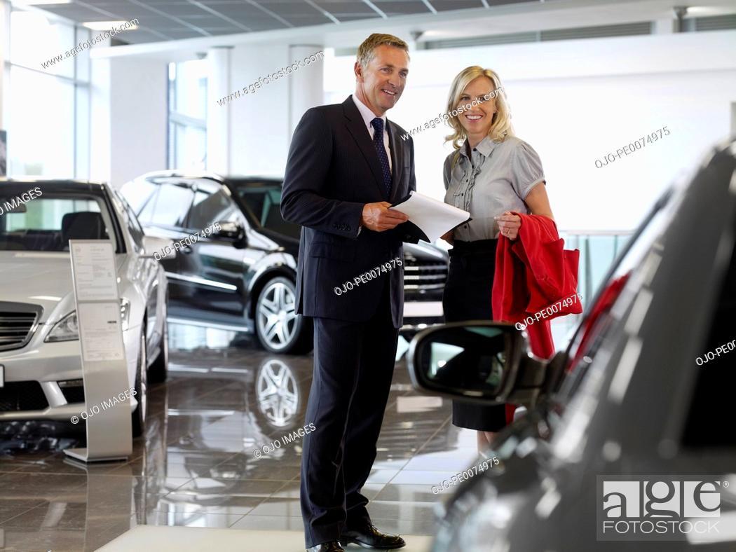 Stock Photo: Salesman talking to woman in automobile showroom.