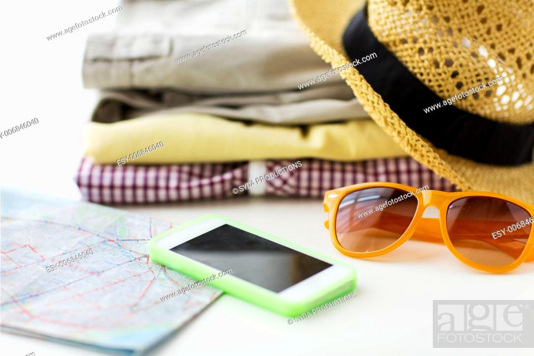 Stock Photo: travel, summer vacation, tourism and objects concept - close up of folded clothes, smartphone and touristic map on table at home.