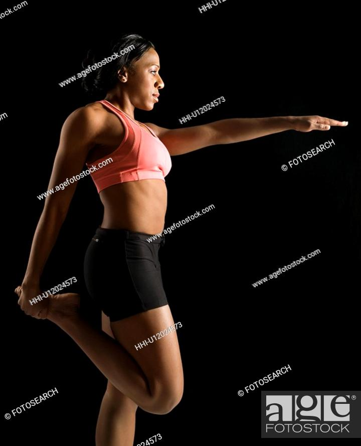 Stock Photo: Profile of African American young adult woman stretching leg with arm raised.