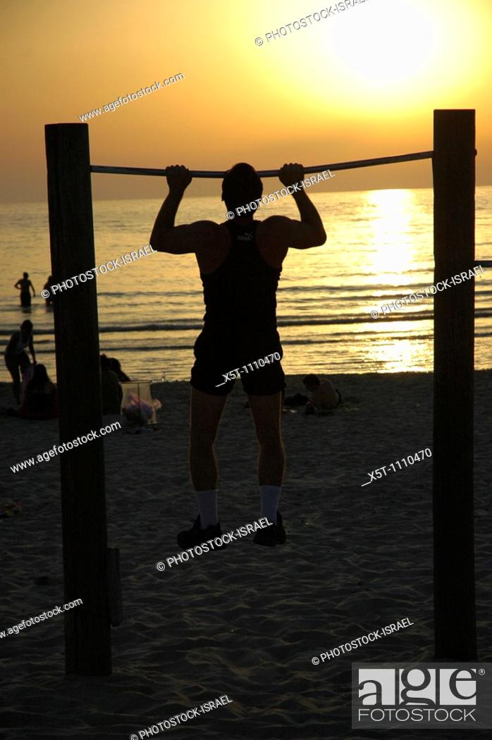 Stock Photo: Israel, Tel Aviv, Physical work-out at sunset a man doing chin ups on the beach at sun set.