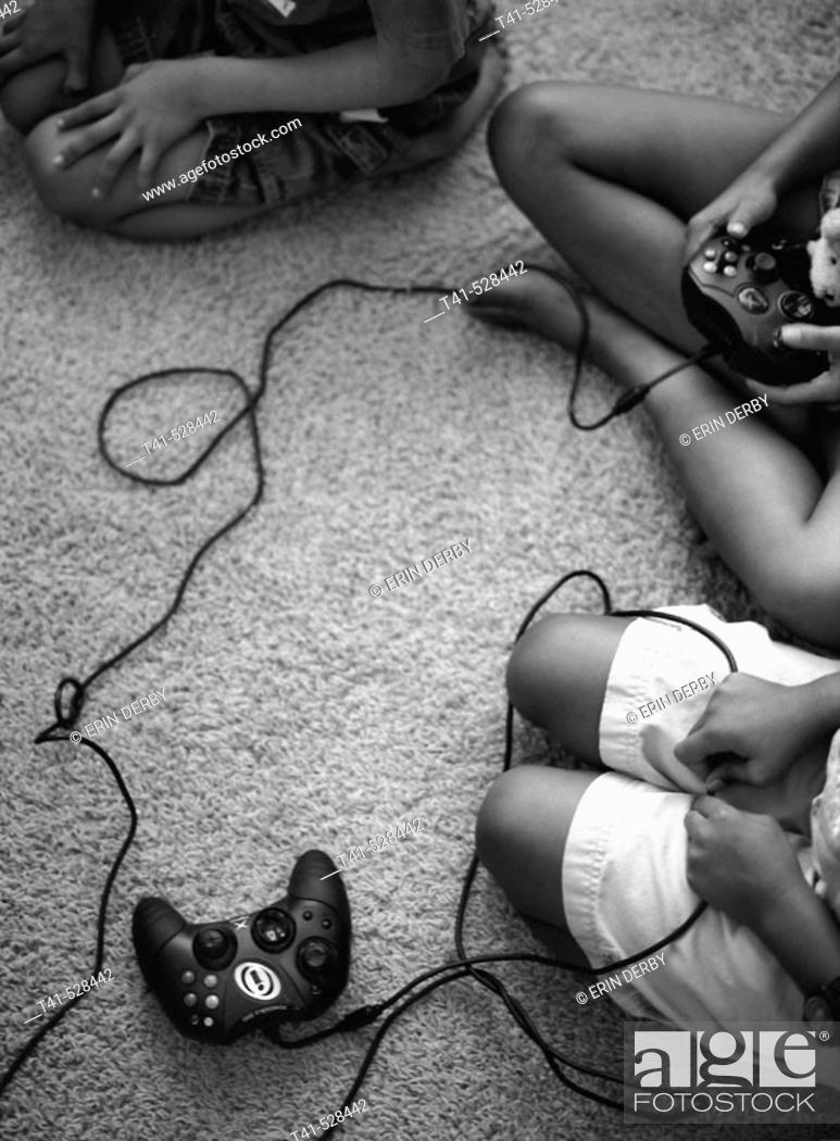 Stock Photo: Brothers and sisters sit on the rug playing video games. Some anxiously await the turn at the remote. All watch the TV.