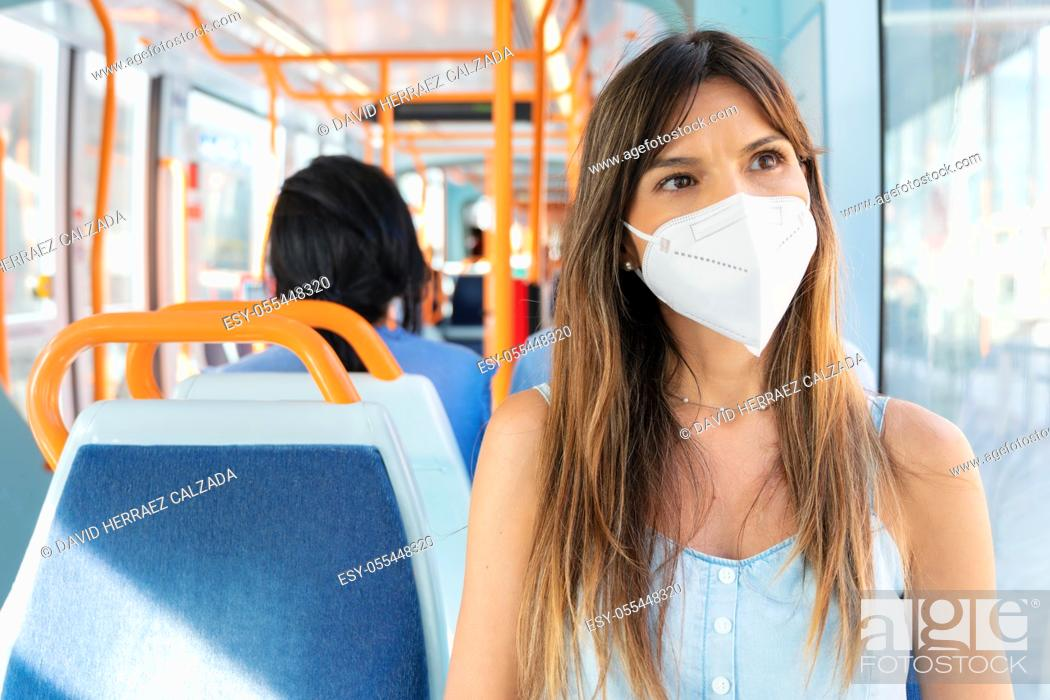 Stock Photo: Young Woman Wearing a Face Mask Riding Public Transport. High quality photo.